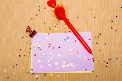 estrellas sparlking coloridas, corazones con la pluma roja y lunas en el papel rosado y el fondo amarillo Fotografía de archivo libre de regalías