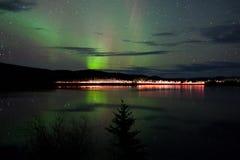 Estrellas y luces norteñas sobre el camino oscuro en el lago Fotos de archivo