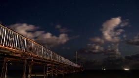Estrellas y nubes de mudanza sobre el embarcadero el vídeo de time lapse 4K de la noche de estrellas con las nubes en la playa en almacen de metraje de vídeo