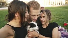 Estremamente chiuda su di tre amici caucasici - due donne, il giovane ed il piccolo cane stanno posando per la macchina fotografi video d archivio