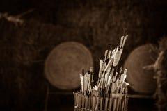 Estremecimiento de flechas delante de blancos de la paja Foto de archivo