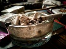 Estremità di sigaretta su un portacenere fotografia stock