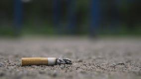 Estremità di sigaretta sulla fine della strada su stock footage