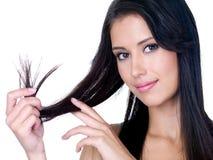 Estremità sorridente della holding della donna dei suoi capelli lunghi Fotografia Stock