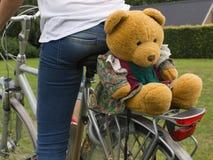 Estremità sulla bici con l'orsacchiotto divertente, vista posteriore, conteggio della giovane donna immagini stock