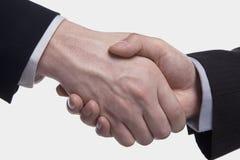 Estremo vicino su di due uomini d'affari che stringono le mani, colpo dello studio Immagini Stock
