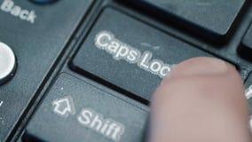 Estremo vicino su di un dito che preme il ` della serratura di cappucci del ` su una tastiera stock footage