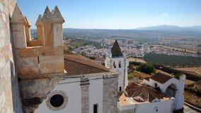 ESTREMOZ, PORTUGAL: Vista da torre das três coroas Torre DAS Tres Coroas com Santa Maria Church no primeiro plano Imagens de Stock Royalty Free