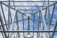 Estructura del bastidor de acero del tejado con el cielo azul y las nubes Foto de archivo