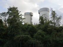 Estructuras industriales entre matorrales verdes foto de archivo