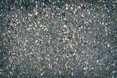 Estrutura áspera do asfalto com muitas pedras coloridas Imagens de Stock