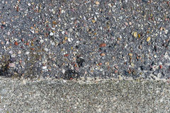 Estrutura áspera do asfalto com muitas pedras coloridas e concreto Fotos de Stock Royalty Free