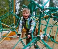 Estrutura de escalada do campo de jogos do menino novo Foto de Stock