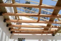 A estrutura de madeira da construção A instalação de feixes de madeira na construção o sistema do fardo do telhado da casa fotografia de stock