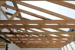 A estrutura de madeira da construção A instalação de feixes de madeira na construção o sistema do fardo do telhado da casa foto de stock royalty free