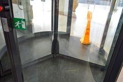 A estrutura de vidro revolvendo da três-porta da construção do shopping da porta ancorou o eixo central e o sinal de giro ao asso imagens de stock royalty free