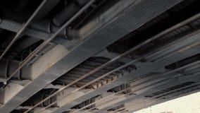 Estrutura do metal do fardo sob a ponte com parafusos prisioneiros e colunas de apoio filme