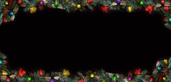A estrutura do Natal, o fundo preto decorado com bolas e ramos de árvore e o espaço para um cumprimento text foto de stock royalty free