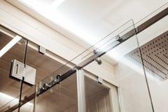 Estrutura mais próxima do metal dos prendedores e dos rolos superiores para a porta de vidro de deslizamento no chuveiro foto de stock royalty free