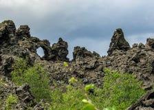 Estruturas pretas dramáticas da rocha da lava, formações vulcânicas originais do fluxo e floresta islandêsa verde, área de Myvatn imagens de stock royalty free
