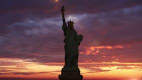 A estátua da liberdade, lapso de tempo do nascer do sol O raio de sol ilumina a tocha da estátua da liberdade animation vídeos de arquivo