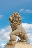 Estátua de um leão de encontro a um céu azul Fotos de Stock Royalty Free