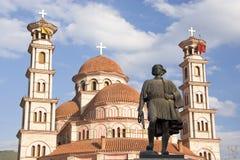 Estátua e igreja ortodoxa, Korca, Albânia Imagens de Stock Royalty Free