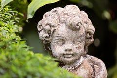 Estátua velha de um anjo infantil ou cupido no jardim Fotografia de Stock