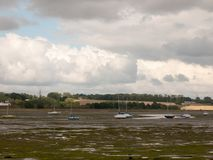 Estuary scene in manningtree with moored boats tide clouds lands Royalty Free Stock Image