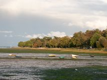 Estuary scene in manningtree with moored boats tide clouds lands Stock Photo