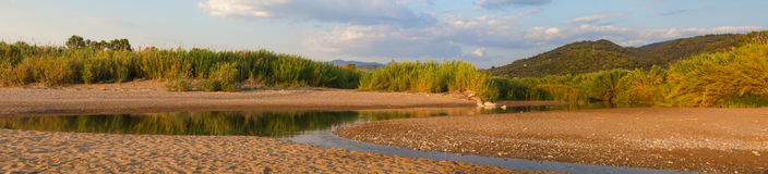 Estuary of a small river on a sandy beach, Greece. Estuary of a small river full of reeds on a sandy beach. Neda river at western Peloponnese, Greece royalty free stock photo
