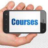 Estudando o conceito: Mão que guarda Smartphone com cursos na exposição Imagens de Stock Royalty Free