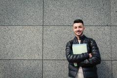 Estudante árabe do moderno que está pela parede de pedra fora Groupmates de espera de sorriso novos do homem fotografia de stock