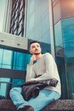 Estudante árabe que espera uma chamada fora Equipe a refrigeração para fora na frente da construção moderna após classes Fotografia de Stock Royalty Free