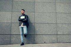 Estudante árabe que guarda cadernos pela parede fora Groupmates de espera do homem novo Fotos de Stock Royalty Free