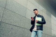Estudante árabe que usa o smartphone fora Homem novo que vai à universidade Foto de Stock Royalty Free