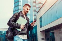 Estudante árabe que usa o smartphone fora O indivíduo feliz olha o telefone na frente da construção moderna após classes Foto de Stock