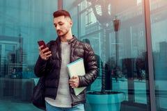 Estudante árabe que usa o smartphone fora O indivíduo sério olha o telefone na frente da construção moderna após classes Fotos de Stock Royalty Free