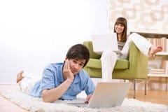 Estudante - adolescente dois com o portátil na sala de visitas Imagem de Stock Royalty Free