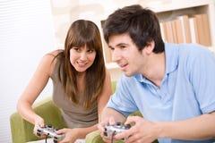 Estudante - adolescentes felizes que jogam o jogo video Fotos de Stock Royalty Free