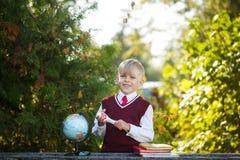 Estudante adorável com livros e globo sobre fora Educação para crianças De volta ao conceito da escola imagens de stock royalty free