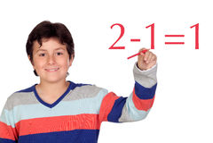 Estudante adorável da criança que escreve uma operação da matemática Foto de Stock