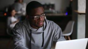 Estudante africano milenar que estuda com livro usando o portátil no café video estoque