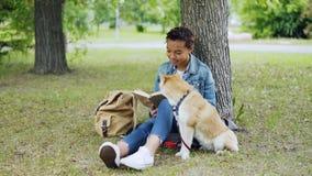 A estudante afro-americano bonita é livro de leitura que senta-se no parque no gramado quando seu cão bem-produzido se sentar per video estoque