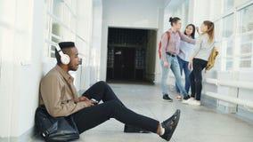 Estudante afro-americano considerável novo que senta-se no assoalho no corredor branco com os fones de ouvido na cabeça que escut filme