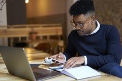 Estudante afro-americano da escola de negócios na camiseta escura e da documentação de contabilidade branca da camisa para no mês fotografia de stock