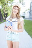 Estudante alegre Girl Holding Books na passagem fotos de stock royalty free