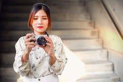 A estudante asiática aprende a fotografia com a câmera de bolso pequena exterior no dia Foto de Stock Royalty Free