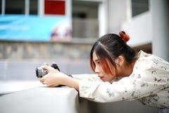 A estudante asiática aprende a fotografia com a câmera de bolso pequena exterior no dia Imagem de Stock Royalty Free