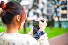 A estudante asiática aprende a fotografia com a câmera de bolso pequena exterior no dia Fotografia de Stock Royalty Free